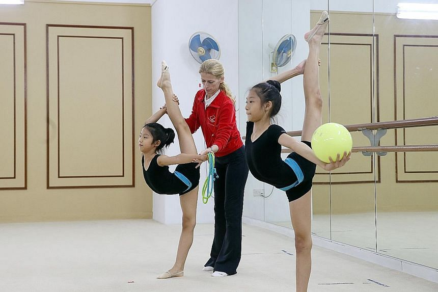 Bianka Panova coaching two of her students at her academy. The Bulgarian believes budding gymnasts can benefit if schools support their training schedules.