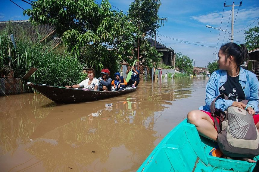 Villagers travelling along a flooded village road in Bandung, West Java, last Friday. According to the study, Indonesia is expected to take the largest chunk of the green investment opportunities in the region.