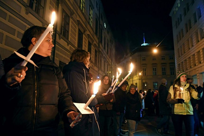 "People hold candles during a rally under the slogan ""Our ministries not in the hands of right-wing extemists"" outside the government buildings in the Austrian capital of Vienna."