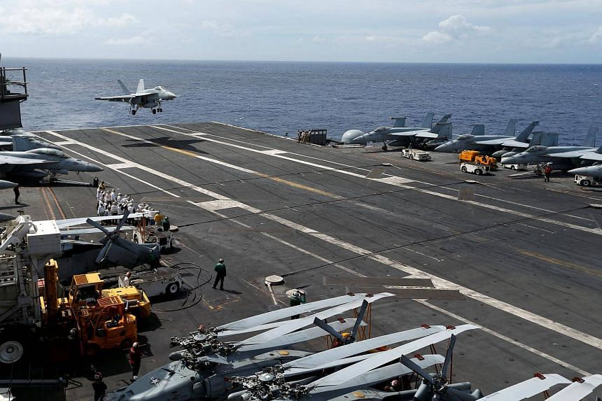 An F/A-18 Super Hornet lands on the deck of the USS Ronald Reagan in the South China Sea.