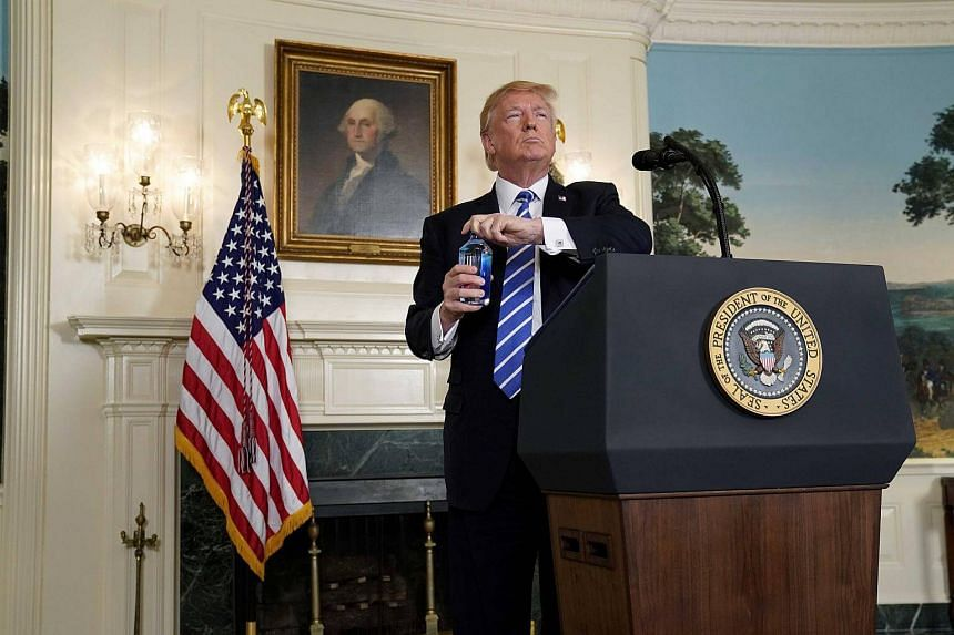 US President Donald Trump prepares to take a drink of water as he speaks about his recent trip to Asia in the Diplomatic Room of the White House in Washington.
