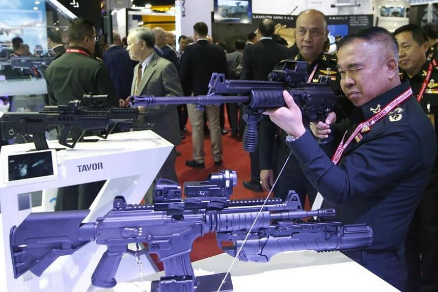 A Thai military officer tests an assault rifle at the Defense and Security 2017 in Bangkok on Nov 6, 2017.