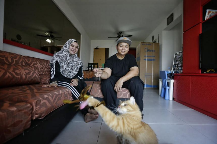 Mr Shah Rizal Abdul Razak and his wife Haryati Ali with their cat Bobo in the flat that was temporarily offered to them by a neighbour who is working overseas.