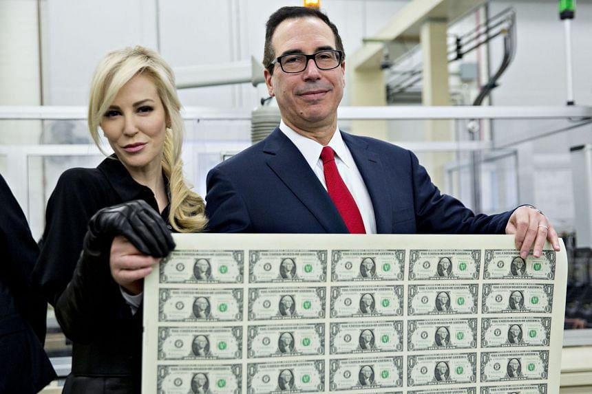 US Treasury Secretary Steven Mnuchin and wife, Louise Linton, hold an uncut sheet of $1 dollar notes.