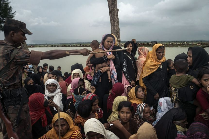 Rohingya refugees awaiting aid after crossing the Naf River into Bangladesh from Myanmar.