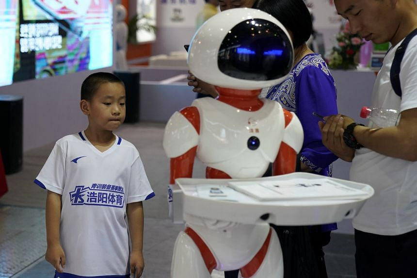 Visitors looking at a robot at the China International Robot Show in Shanghai in July. The city's plan to become an artificial intelligence hub outlines 21 measures to boost the industry.