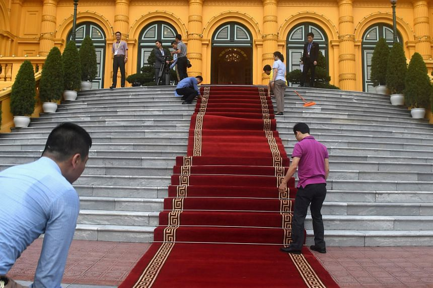 Workers preparing for US President Donald Trump's state visit to Hanoi on Sunday. His visit was followed hours later by Chinese President Xi Jinping's arrival.