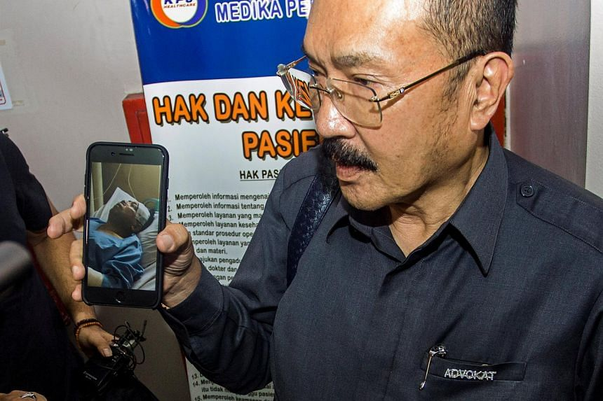 Fredrich Yunadi, the lawyer for Indonesia's Speaker of the House Setya Novanto, shows a picture of Novanto being treated in a hospital following a car accident in Jakarta on Nov 16, 2017.