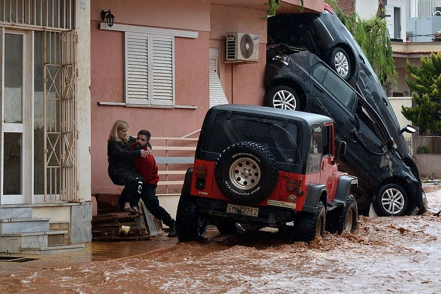 """A man helping evacuate a woman from a flooded street in Mandra, north-west of Athens, yesterday after heavy rain left 15 people dead. On Wednesday evening, Prime Minister Alexis Tsipras declared a day of national mourning. """"This is a very difficult t"""