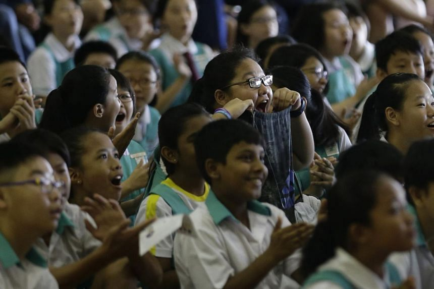 Pupils at Zhonghua Primary School reacting as the school's overall PSLE results were revealed on Nov 24, 2016.
