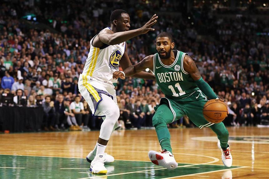 Kyrie Irving #11 of the Boston Celtics drives against Draymond Green #23 of the Golden State Warriors.