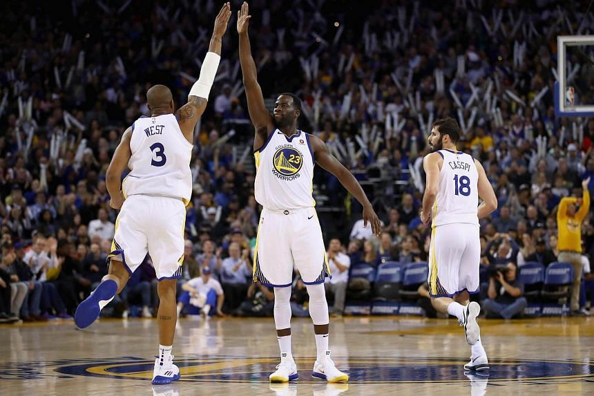 Draymond Green (#23) high-fives David West (#3) of the Golden State Warriors during their game against the Orlando Magic at ORACLE Arena in Oakland, California.