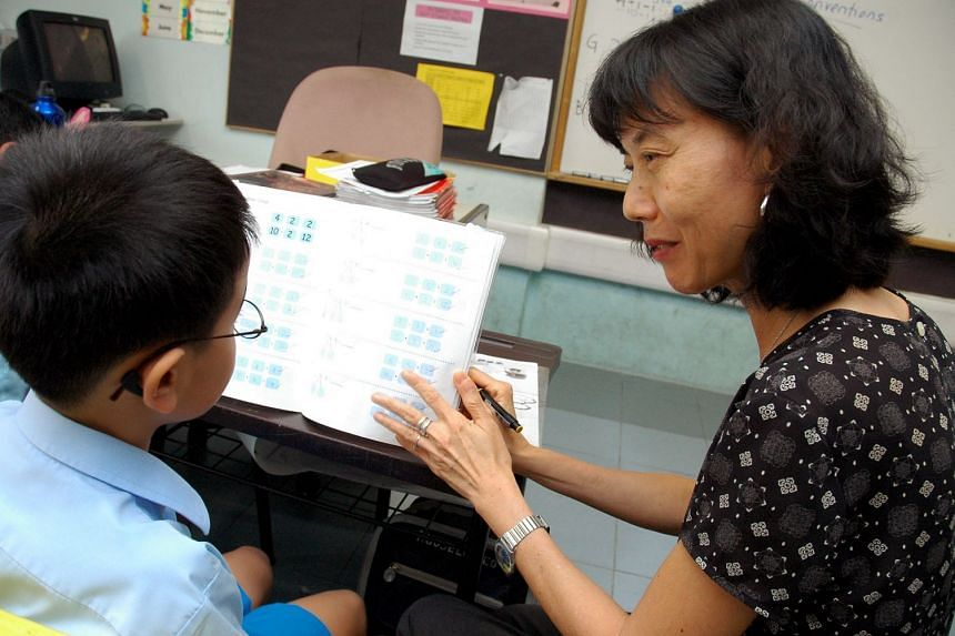A special needs officer at Yangzheng Primary School helping a child with his work.
