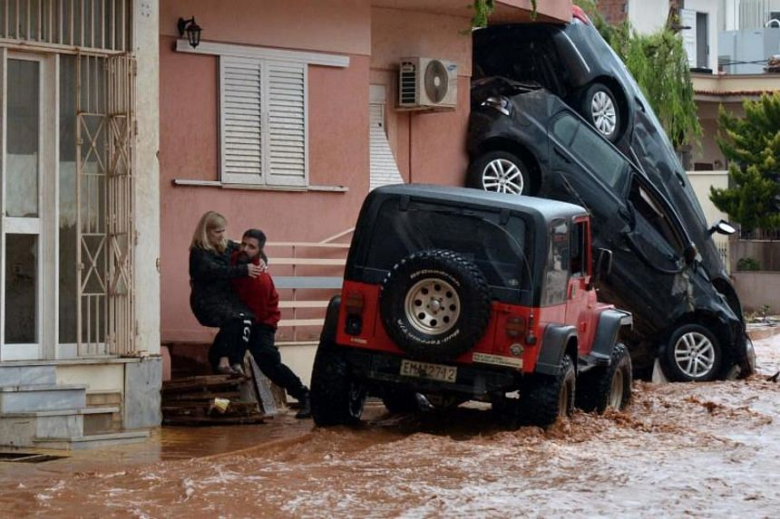 A man helps evacuate a woman from a flooded street in Mandra, northwest of Athens, on Nov 16, 2017.