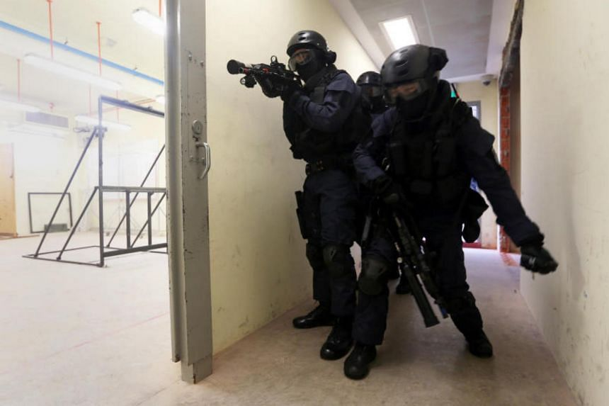 Before the Spear Force team gains entry into a mock workshop, a member of team tosses a flash bang, or what's known as a stun grenade, to disorientate the rioting inmates inside a mock workshop.
