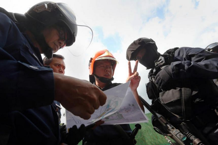 Senior Chief Warder 2 Zainal Haron, 53, in full tactical gear and balaclava, listens in to prison ground commanders when the Spear Force is activated to evacuate inmates during a mock fire.