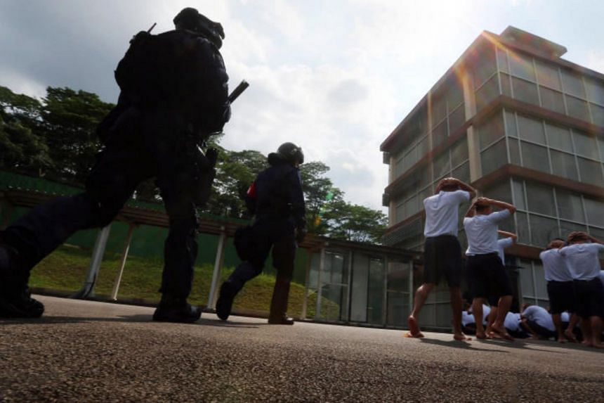 """The 50 inmates are evacuated to a safer part of the prison unaffected by the """"fire"""". Forming a security cordon are armed officers from the Spear Force, who work alongside the Crisis Support Team from Admiralty West Prison."""