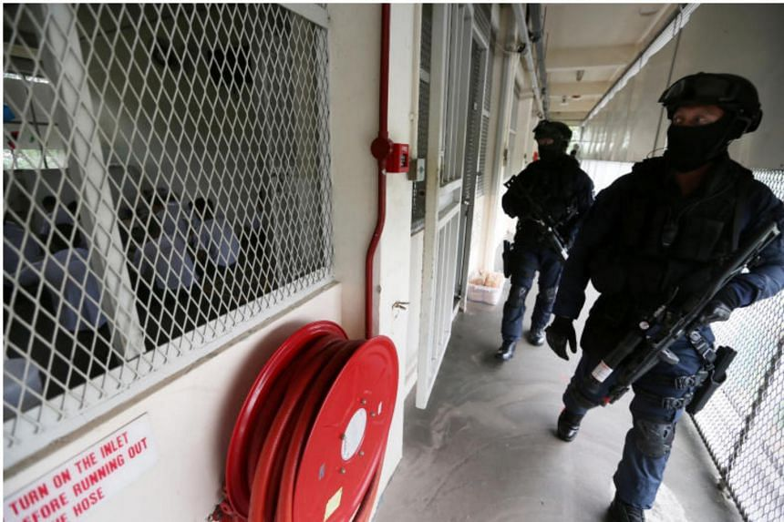 """In a move that's known as a """"show of force"""", Spear Force officers make their presence known by walking along the corridors of a prison block in Admiralty West Prison. This is ensure that inmates comply with instructions."""