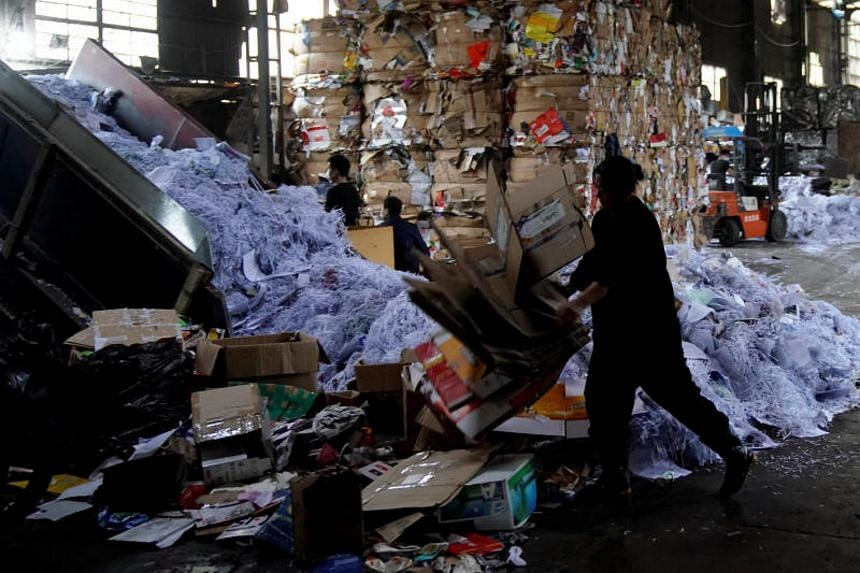 Labourers work at a paper products recycling station in Shanghai, China on Nov 17, 2017.