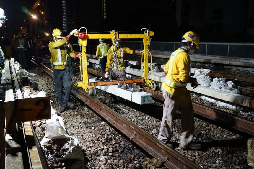 SMRT said it would not have been able to complete the change out of all the power rails and 188,000 sleepers if staff count had indeed been cut. PHOTO: SMRT