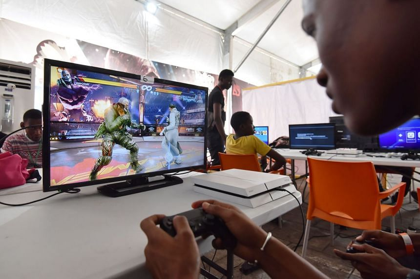 A man plays a video game during a festival of electronics and video games.