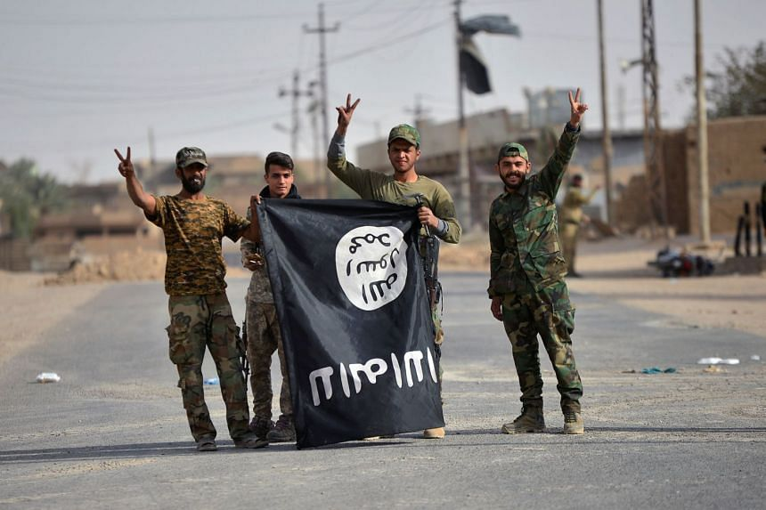 Shi'ite Popular Mobilization Forces (PMF) fighters carry the Islamic State in Iraq and Syria (ISIS) militants' flag downward after liberating the city of Al-Qaim, in Iraq, on Nov 3, 2017.