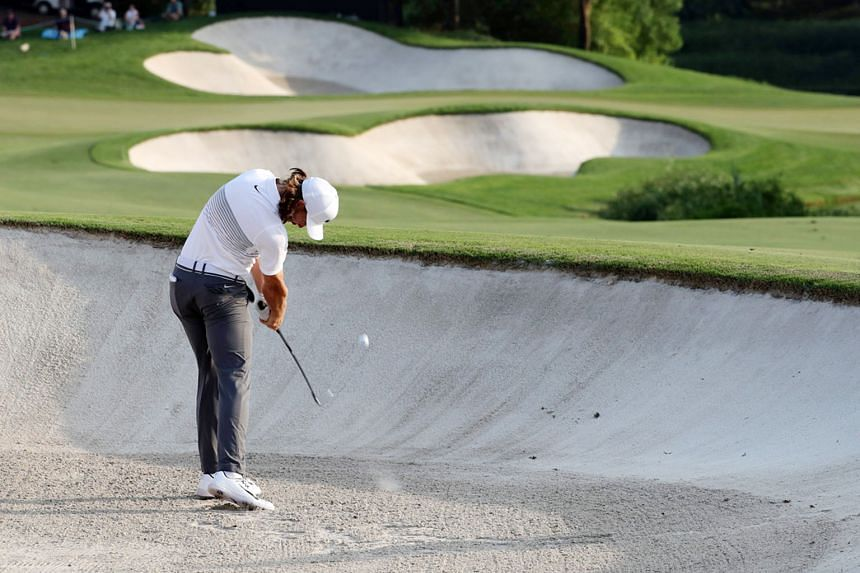 England's Tommy Fleetwood (above) playing a bunker shot during the first round of the DP World Tour Championship at Jumeirah Golf Estates in Dubai yesterday. The world No. 19 had a disastrous opening and handed Justin Rose (left) the initiative in th