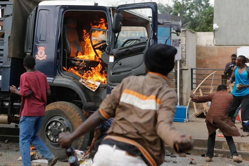 An opposition supporter aims a bow and arrow at police as he and others attack and burn a police truck.