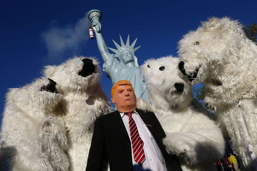 A protester wears a Donald Trump mask and others dress as polar bears ahead of the UN Climate Change Conference.