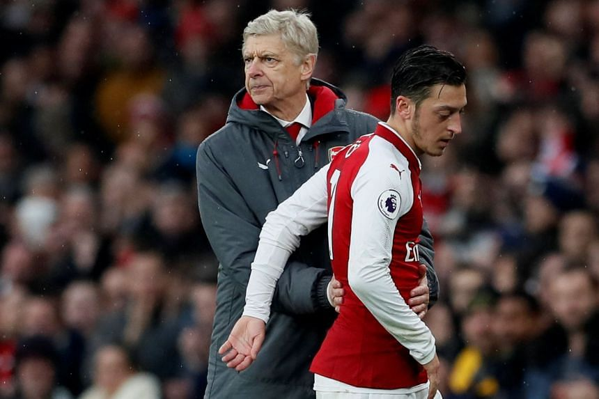 Arsenal's Mesut Ozil with Arsenal manager Arsene Wenger after being substituted.