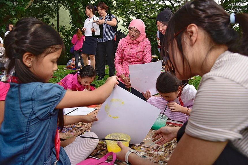 President Halimah Yacob observing children creating bubble art yesterday at the Istana. More than 30 children from the Dyslexia Association of Singapore were invited by Madam Halimah to the picnic, where they had light refreshments on the lawn and pa