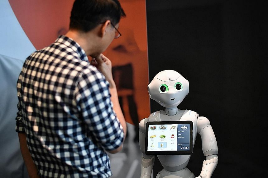 Pepper (above), a humanoid robot, can be found at the Innovation Showcase area of Mastercard's Asia-Pacific headquarters in Singapore. Staff at the company also get work desks (left) whose heights can be adjusted.