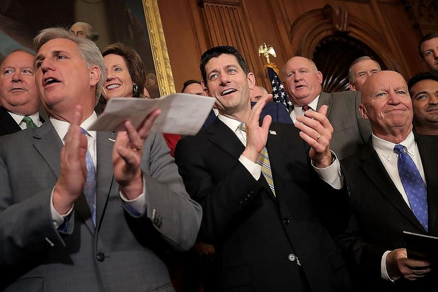House Speaker Paul Ryan (at centre) with fellow House Republicans after the passage of the tax cut Bill at the US Capitol on Thursday.