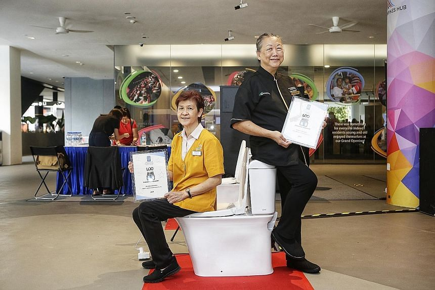 Cleaning assistants Tan Joo Hiang (left) and Yu Lee Wah with their Let's Observe Ourselves (Loo) Awards given by the Restroom Association (Singapore) yesterday.