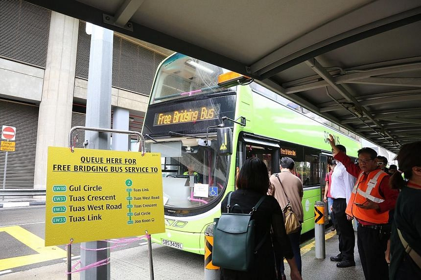 Commuters utilising the free bridging bus service at Joo Koon station yesterday morning. While the four stations on the extension - Gul Circle, Tuas Crescent, Tuas West Road and Tuas Link - will reopen after the weekend, the authorities will keep the