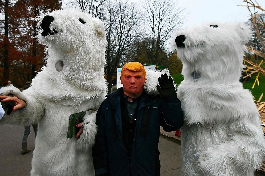 A man wearing a mask of President Donald Trump during the climate change conference in Bonn, Germany, on Thursday. Mr Trump's decision to withdraw the US from the global pact cast a shadow over talks.