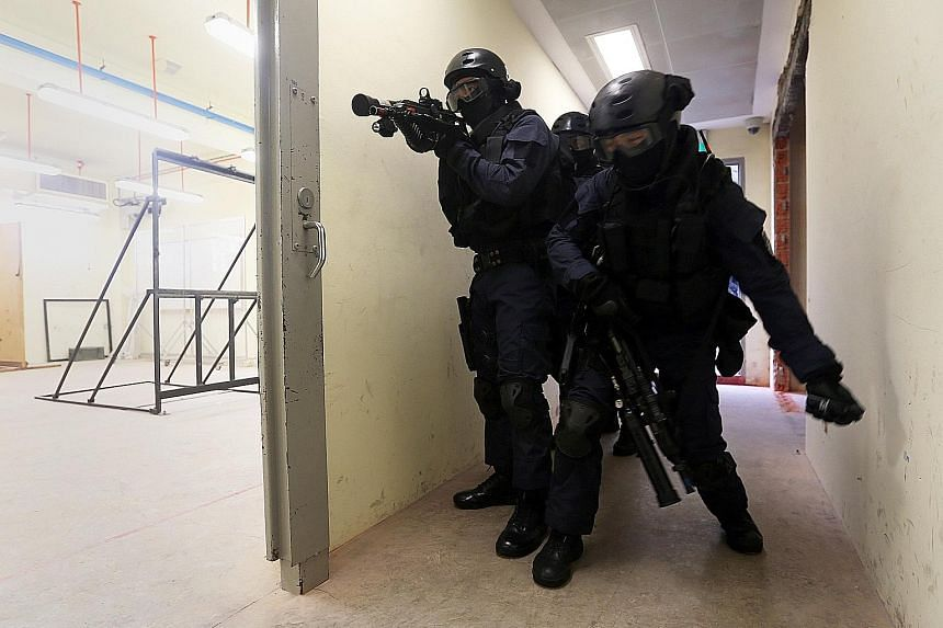 A member of the Spear Force team tossing a flash bang - or what's known as a stun grenade - into a mock workshop to disorientate rioting inmates before the rest of the team enters.