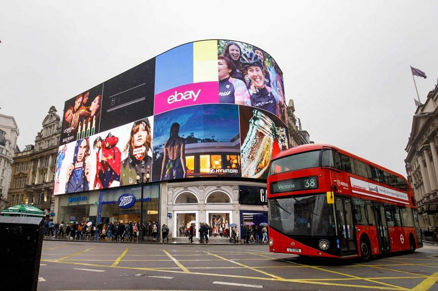A red double decker bus goes past Piccadilly Circus advertisement screens in London.