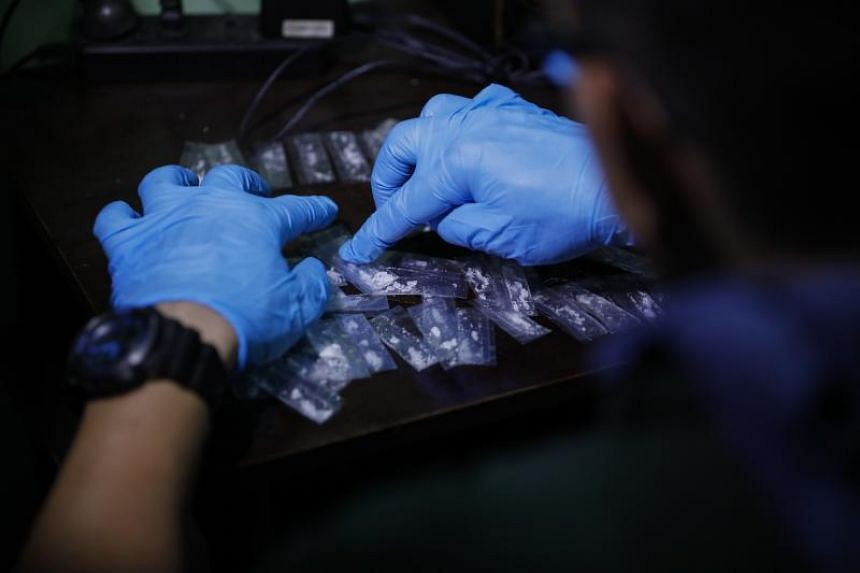 An agent of the Philippine Drug Enforcement Agency (PDEA) finds packets of what is believed to be illegal drugs from the home of a suspected pusher during a raid in Makati City, east of Manila, Philippines on Nov 8 2017.