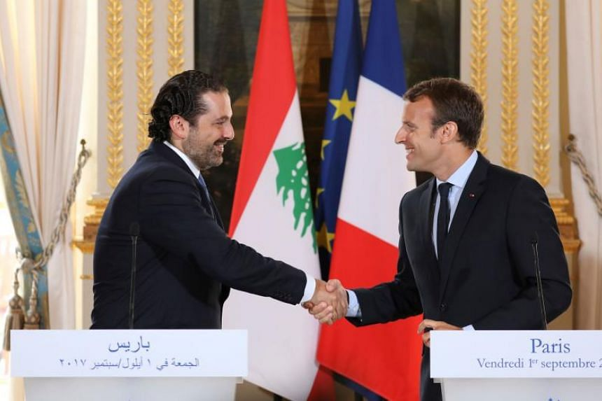 French President Emmanuel Macron (right) shaking hands with Lebanese Prime Minister Saad Hariri during a press conference at the Murat Lounge in the Elysee Palace in Paris, on Sept 1, 2017.