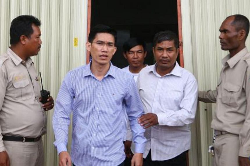 Former RFA reporters Oun Chhin  (centre, back) and Yeang Sothearin (left in blue shirt) are escorted by officials after being detained for questioning in Phnom Penh's Meanchey district yesterday.