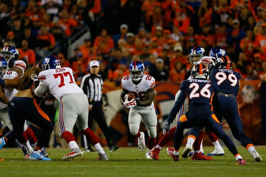 Running back Orleans Darkwa #26 of the New York Giants runs through a hole during the first quarter Denver Broncos at Sports Authority Field at Mile High on Oct 15, 2017 in Denver, Colorado.