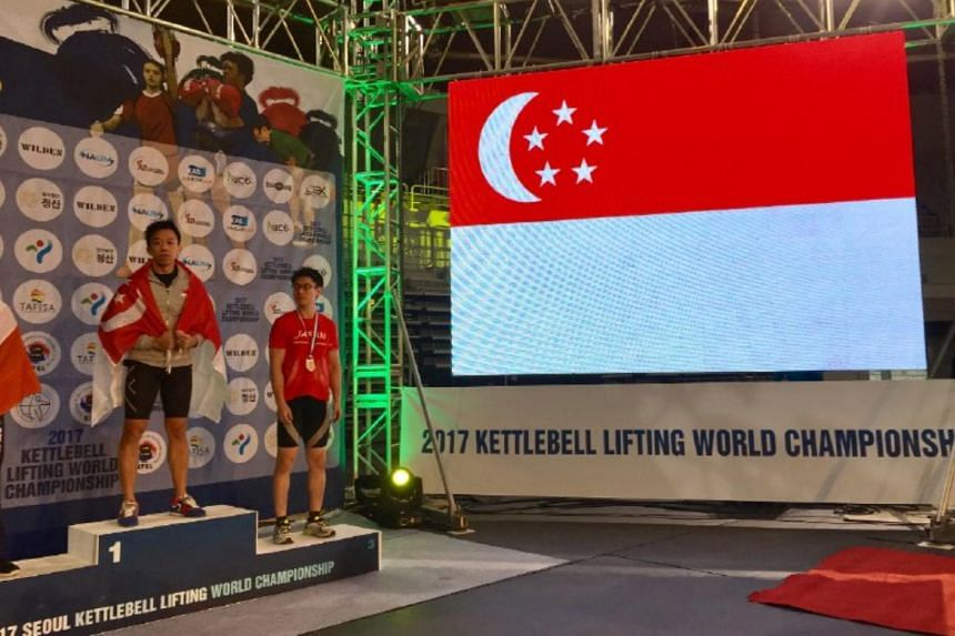 Samuel Lam standing on top of the podium with the Singapore flag draped over his shoulders.