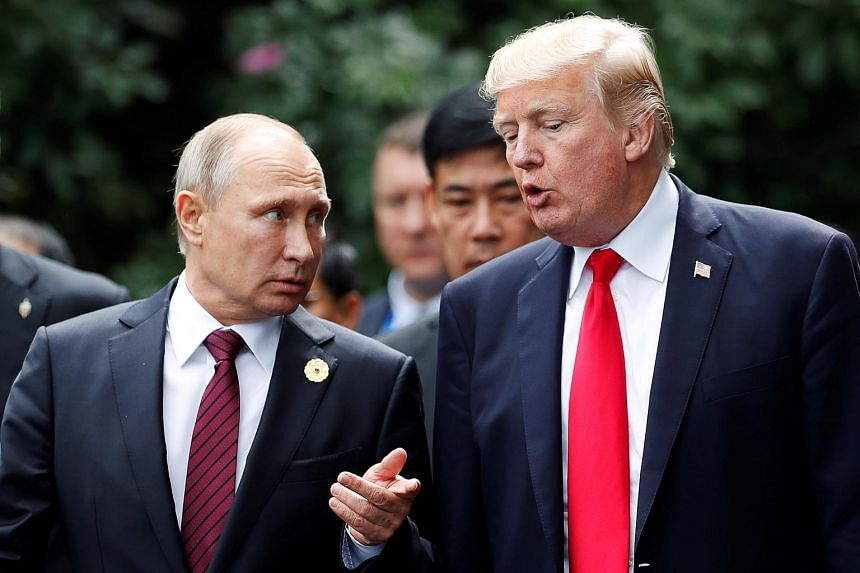 US President Donald Trump and Russia's President Vladimir Putin talk during the family photo session at the APEC Summit in Danang, Vietnam on Nov 11, 2017.