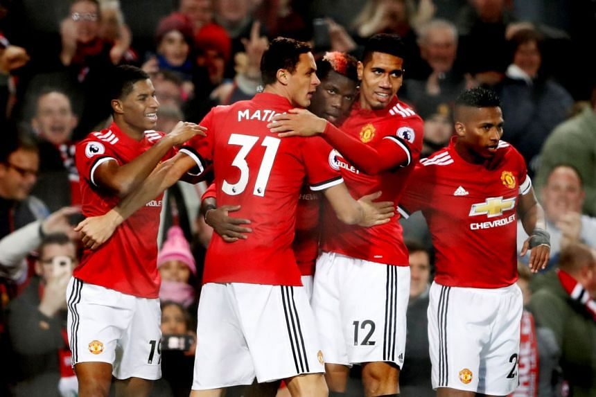 Manchester United's Paul Pogba celebrates with team mates after scoring their third goal.