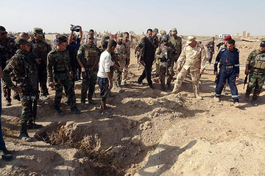 Iraqi forces searching the site of a suspected mass grave of victims killed by ISIS near a former military base, south-west of Hawija.