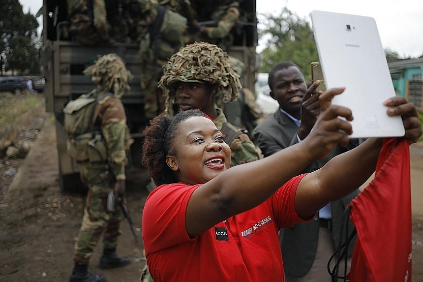 A women taking a selfie with soldiers at an anti-Mugabe rally organised by the War Veterans Association yesterday.