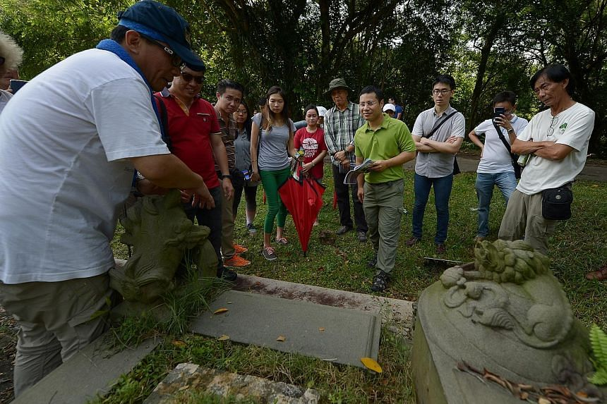 Bukit Brown volunteer Fabian Tee (left), 50, showing Social and Family Development Minister Desmond Lee (in green) yesterday the details of a tomb at the launch of the trail at Bukit Brown Cemetery.