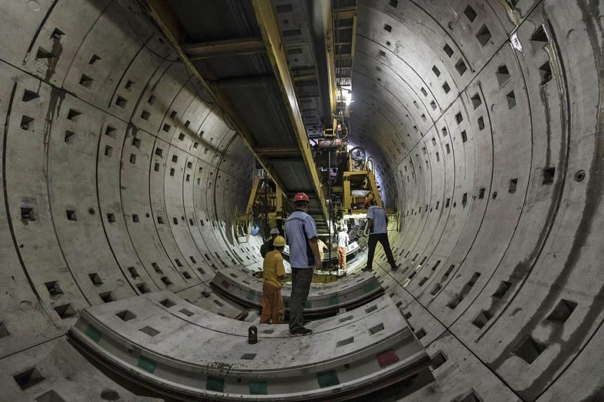 Workers labor beneath a tunnel-boring machine at a construction site for Line 14 of the Shanghai Metro system in China.