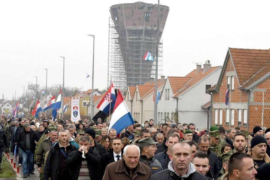 People march in Vukovar during a ceremony to mark the 26th anniversary of the fall of Vukovar to Serb forces.